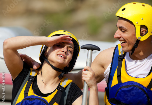 Happy couple rafting equipment