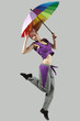 Young and beautiful female jumping high with umbrella