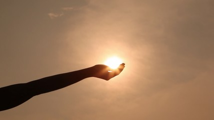 silhouette of hand which brings palm to sun and cleans back