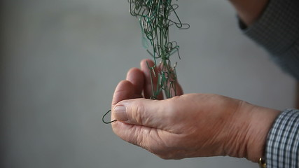 man tries to untangle Christmas ornament hangers