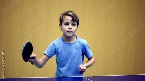 Little boy wearing blue shirt playing ping pong