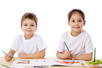 Two little kids draw with watercolor
