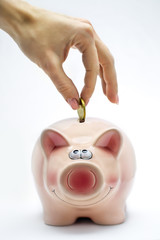 Hand is inserting a coin into pink piggy bank