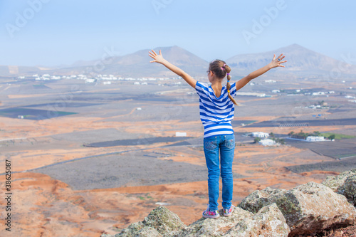 girl standing on cliff's edge, looking to a sky