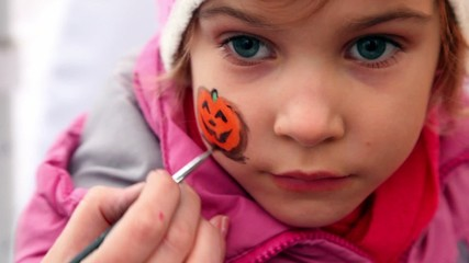 Hand hold brush and draw pumpkin on girls cheek