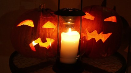 pumpkins of halloween with flame inside and old candle lamp