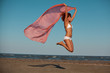 beautiful woman jumping for joy desert beach