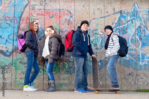Happy teenage friends with school bags and skateboards
