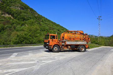 Orange vacuum truck roadside turnout