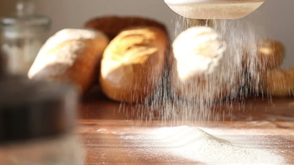 Hand sifts the flour through a sieve, slow motion, dolly shot