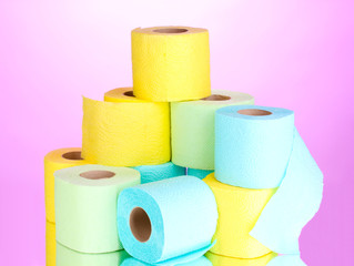 bright rolls of toilet paper on pink background