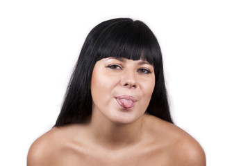 Portrait of young brunette woman with her tongue out