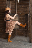 CowGirl standing in saloon entrance poster