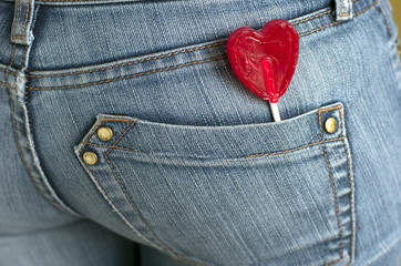 Piruleta con forma de corazón, pantalón tejano.