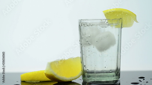 Shot glass filled with clear alcohol and lime