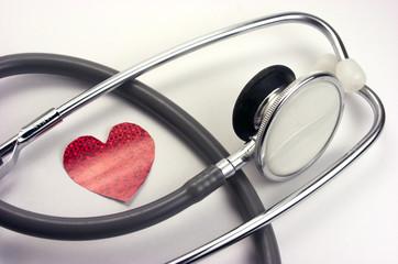 Fonendoscopio, corazón rojo de papel.