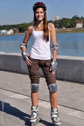 canvas print picture Huebsche Sportlerin steht auf Inline-Skater
