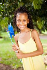 happy indian little girl with pinwheel outdoors