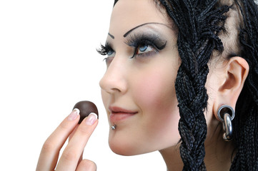 young stylish woman with dreadlocks, holding chocolate candy