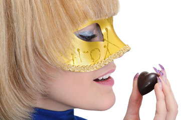 young woman in carnival mask hold chocolate candy