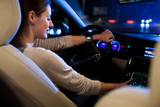 Fototapety Driving a car at night -  young woman driving her modern car