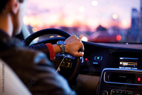 canvas print picture Driving a car at night - young man driving her car