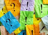 Frage- u. Ausrufezeichen auf bunten zerknüllten Zetteln