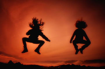 Jumping girls having fun at sunset