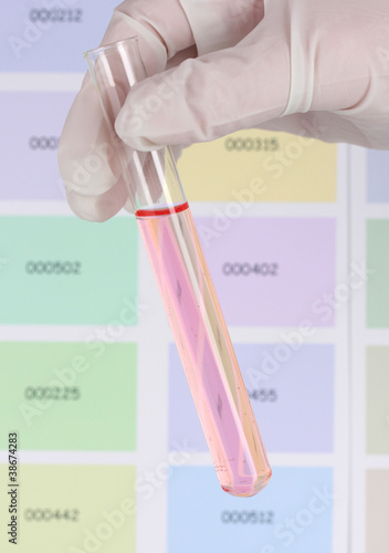 Tube with pink liquid in hand on color samples background