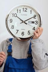 Mann haelt eine Uhr vor seinem Gesicht als Symbol für Zeitarbeit