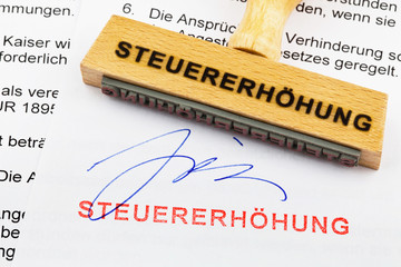 Holzstempel auf Dokument: Steuererhöhung