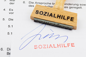 Holzstempel auf Dokument: Sozialhilfe