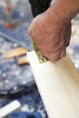 Handwerker schraubt Winkelstück an Holz an
