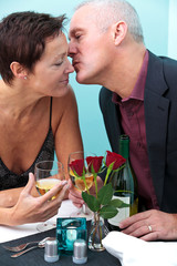 Mature couple restaurant kiss