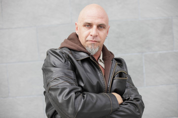 Man with arms crossed in a leather jacket