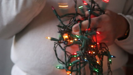 man untangling colored Christmas lights