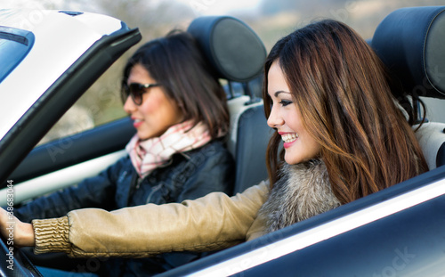 two girls in a convertible car