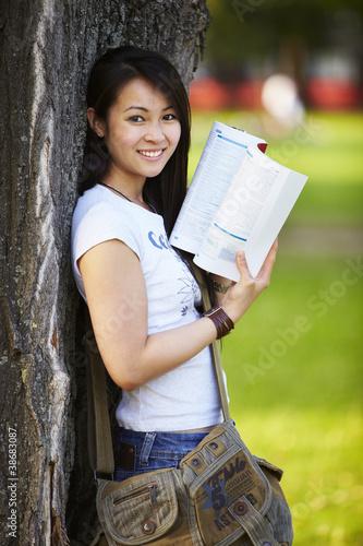 Mädchen steht am Baum, lernen