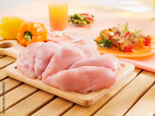 Fresh raw chicken breast arrangement on kitchen cutting board