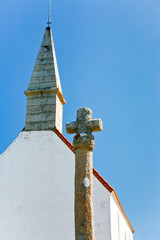 old stone cross and roof of country chapel