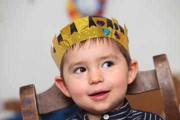 Kind mit Geburtstagskrone auf einem Stuhl sitzend