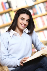smiling female student with book in hands in a bookstore - model