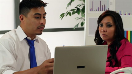 Hispanic coworkers talking about information on laptop.
