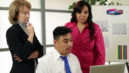 Businesswoman and Hispanic co-workers discuss data on laptop.