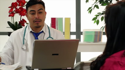 Hispanic doctor in his office talks to woman