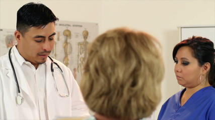 Hispanic Doctor and Nurse Talk to Patient