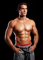 handsome powerful muscular man isolated on black