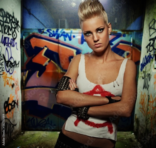 Punk girl on graffiti painted gateway