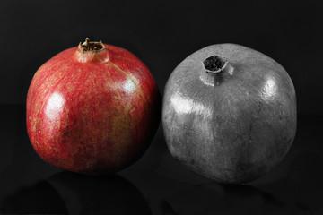 Two ripe pomegranates on black background