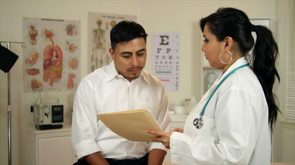 Latina Doctor in clinic shows patient lab results